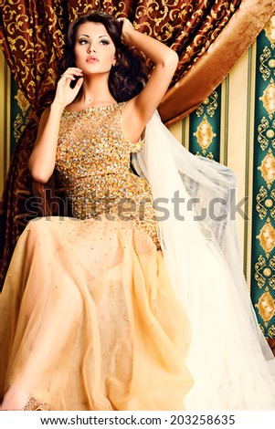 Fashion shot of a stunning woman in luxurious golden dress.  - stock photo