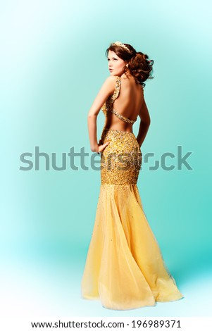 Fashion shot of a stunning woman in luxurious golden dress. Full length portrait. - stock photo