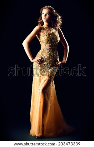 Fashion shot of a stunning woman in luxurious golden dress. Over black background. - stock photo