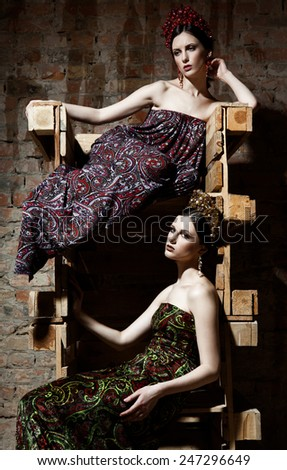 Fashion shot of a two twin sisters in dresses - stock photo