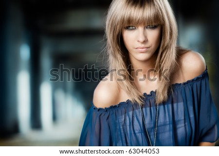 fashion shot of a young, blonde woman, with blue blouse and naked shoulders - stock photo