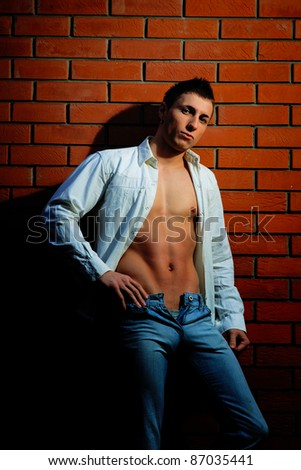 Fashion shot of a young handsome man in casual glamour clothes near the brick wall.