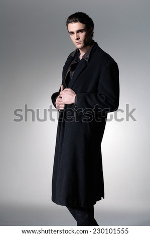 Fashion Shot of a young man in black coat on light background