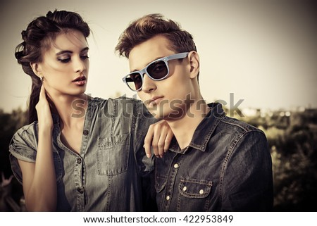 Fashion shot of an attractive young couple in jeans clothes posing outdoor. Toned photo, sepia. - stock photo