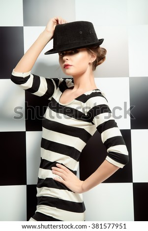 Fashion shot of an elegant model posing in dress in black and white stripes on a background of black and white squares. Beauty, fashion concept. - stock photo
