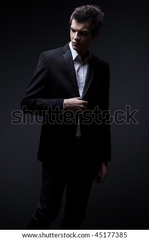 fashion shot of an elegant young man wearing suit - stock photo