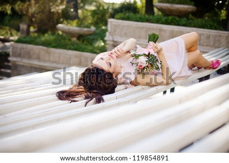 Fashion shot of beautiful girl in stylish dress with a bouquet of flowers in her hands - stock photo