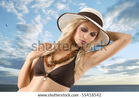 fashion shot of blond young girl in bikini swimsuit posing with hat against a cloudy sky