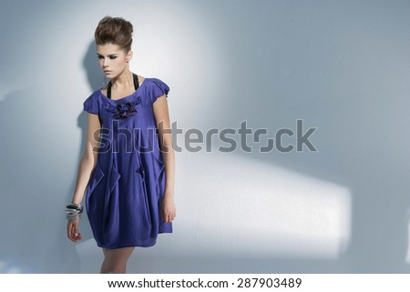 fashion shot of girl in sundress posing in light background  - stock photo