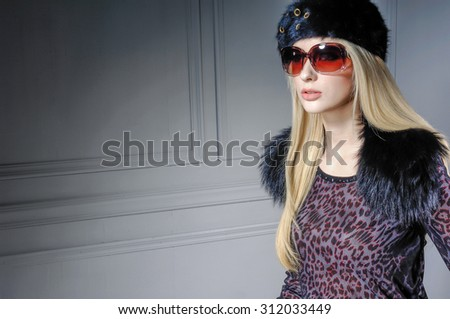 fashion shot of girl in sunglasses ,with hat posing in studio - stock photo