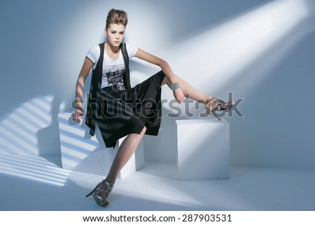fashion shot of girl sitting cube posing in light background  - stock photo