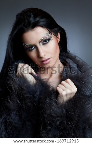 Fashion shot of glamorous woman with jewelry make-up and coat