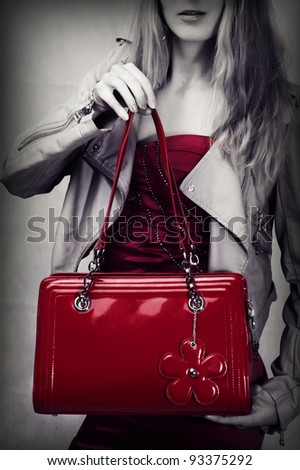Fashion shot of red patent leather bag in woman hands - stock photo