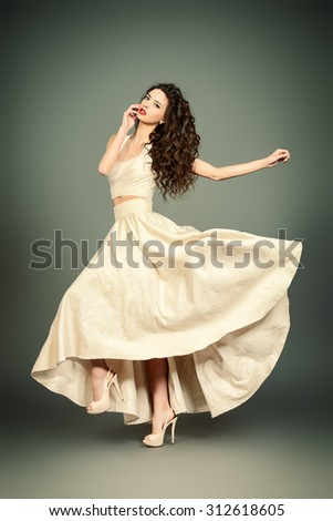 Fashion shot of the elegant woman in beautiful long dress posing in motion. Studio shot. - stock photo