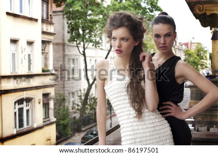 fashion shot of two attractive and elegant girl friend outside in a balcony with old fashion style building in background - stock photo