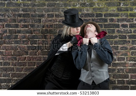Fashion shot of woman  dressed as Jack the Ripper strangling man