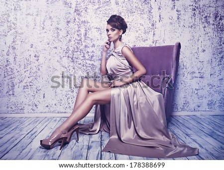 Fashion shot of young beautiful woman in gorgeous silk dress sitting in antique armchair - stock photo