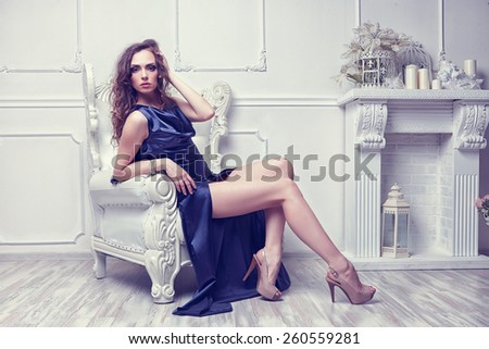 Fashion shot of young beautiful woman in long blue dress sitting in antique armchair