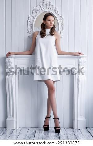 Fashion shot of young beautiful woman in white short dress posing near antique fireplace - stock photo