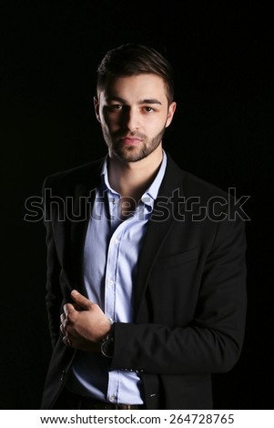 fashion shot of young man model wearing shirt and black jacket on black background