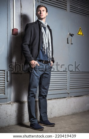 Fashion shot: portrait of a handsome young man wearing jeans and coat  - stock photo