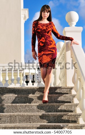 fashion slim girl standing on the stairs - stock photo