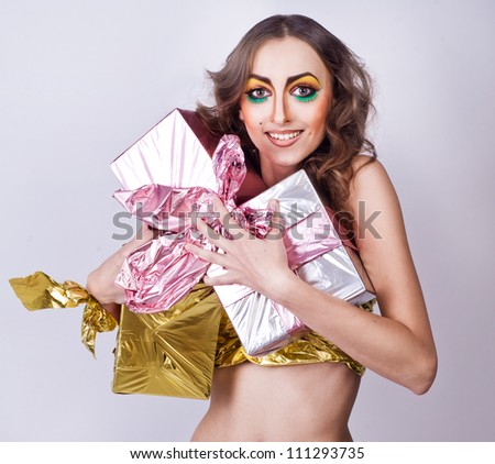 fashion smiling woman model with beauty bright make-up posing in studio with presents. Beautiful famale face with clean skin. - stock photo