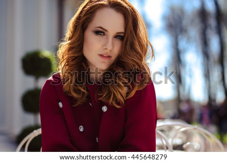 fashion street photo session of stylish young lady in a casual clothes in a summer cafe