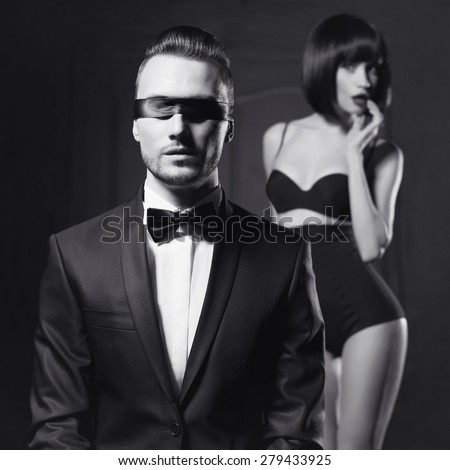 Fashion studio photo of a sensual couple in lingerie and a tuxedo - stock photo