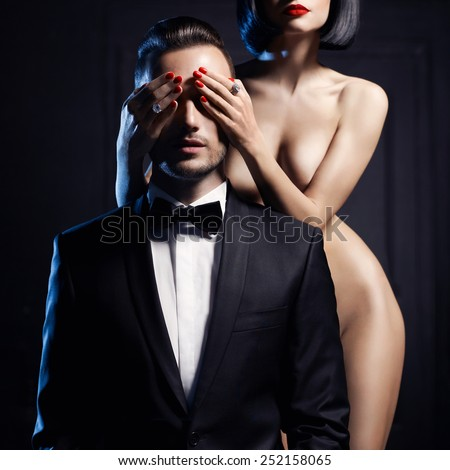 Fashion studio photo of a sensual couple on black background - stock photo