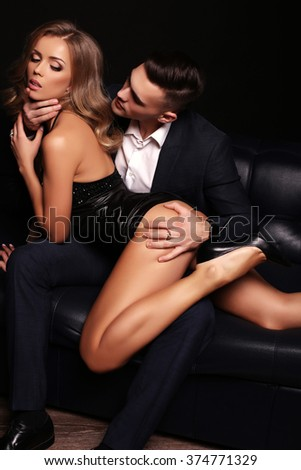 fashion studio photo of beautiful couple. gorgeous woman with long blond hair posing with handsome brunette man in elegant suit - stock photo