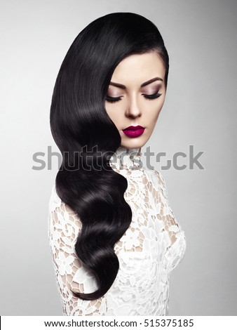 Fashion studio photo of beautiful model girl brunette with long curled hair and red lips. Hairstyle Hollywood wave. Wedding image hairstyle. Perfect makeup. Healthy hair. Long dark magnificent hair