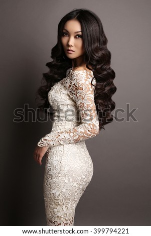 fashion studio photo of beautiful sensual asian woman with long dark hair in elegant lace dress - stock photo