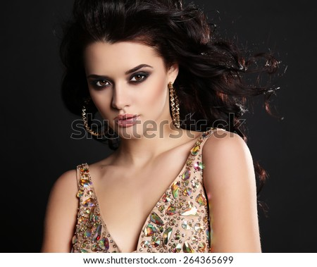 fashion studio photo of beautiful sensual woman with dark hair and bright makeup wearing luxurious sequin dress - stock photo
