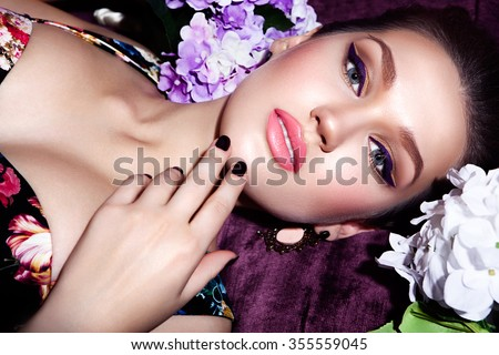 fashion studio photo of beautiful sensual woman with dark hair and bright makeup,with flowers