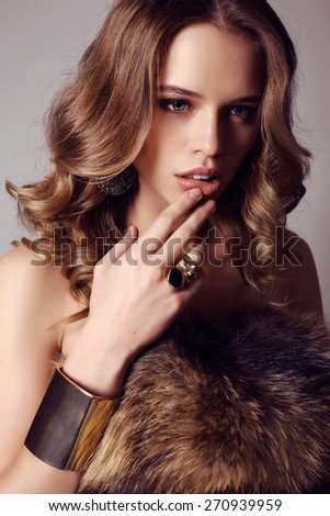 fashion studio photo of beautiful sensual woman with dark hair in elegant gold dress