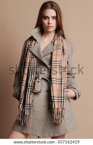 fashion studio photo of beautiful woman with dark hair in elegant wool coat  - stock photo