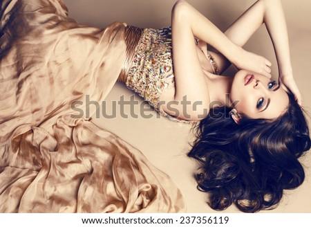 hình ảnh studio thời trang của cô gái trẻ xinh đẹp với mái tóc đen mặc sang trọng váy màu be, nằm trên sàn nhà tại studio
