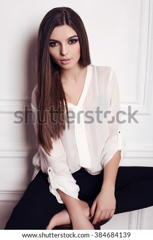 fashion studio photo of beautiful young woman with dark straight hair and evening makeup, wears elegant blouse - stock photo