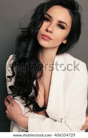 fashion studio photo of gorgeous sexy woman with dark hair and evening makeup