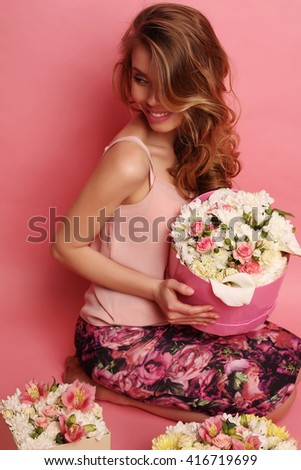 fashion studio photo of gorgeous woman with dark hair in elegant clothes posing with bouquet of flowers