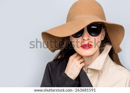 Fashion studio photo of stylish lady in hat and sunglasses. Closeup portrait of woman wearing felt hat - stock photo