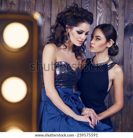 fashion studio photo of two beautiful sensual women with dark hair in luxurious dresses with bijou