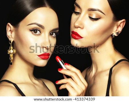 Fashion studio photo of two beautiful young ladies with red lipstick. Perfect face makeup. Beauty and jewelry  - stock photo