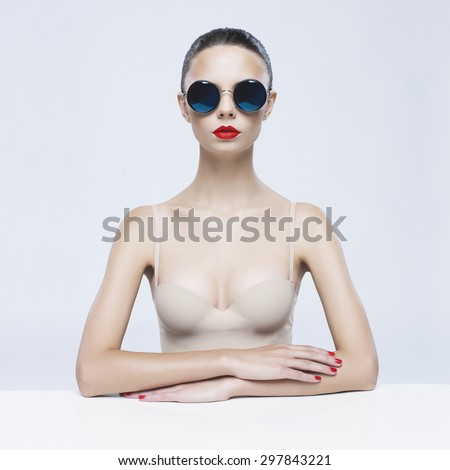 Fashion studio photo of young elegant lady in sunglasses - stock photo