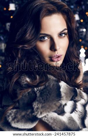 fashion studio portrait of beautiful sensual woman with dark hair in luxurious black hair posing on Christmas tree background - stock photo