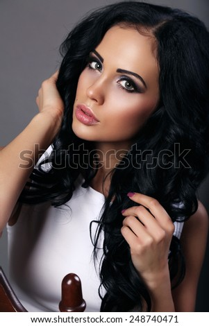 fashion studio portrait of beautiful woman with dark hair wearing elegant  dress