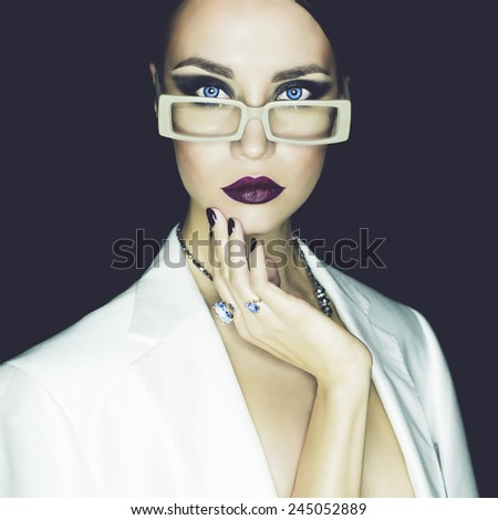 Fashion studio portrait of beautiful woman with glasses - stock photo