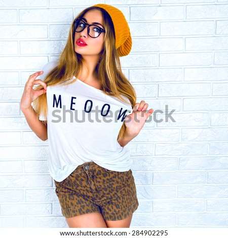 Fashion studio portrait of beautiful young blond hair women making face a cap, white t-shirt and shorts with glasses and red lips against a white wall. - stock photo