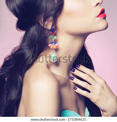 Fashion studio portrait of beautiful young woman with earring. Beauty and manicure. Jewelry and accessories - stock photo
